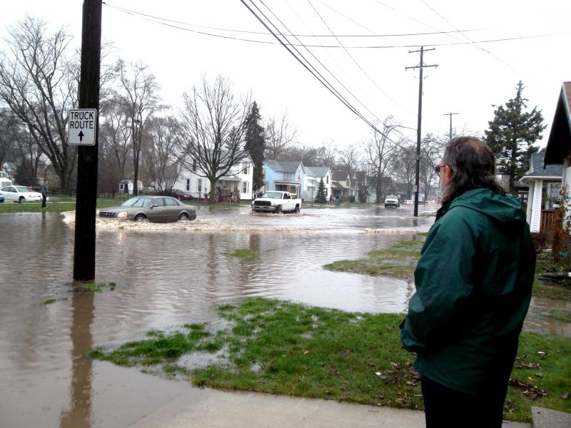 Mike Seibold watches cars drive through a closed road near his house Thursday afternoon in Grand Rapids.