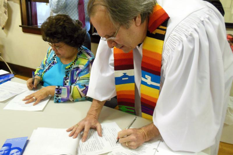 Reverend Bill Freeman signs marriage license and performs cermonies at Harbor Unitarian Universalist Congregation in Muskegon.