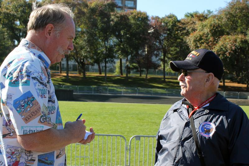 Neil Haglund asks WWII veteran Tom Bates for his autograph at the memorial of the battle of Iwo Jima.