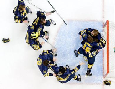 Wolverine players swarm goalie Shawn Hunwick after U-M won the CCHA hockey tournament to keep alive its streak of 20 consecutive NCAA playoff appearances.