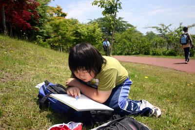 School student in Japan reading a book outside