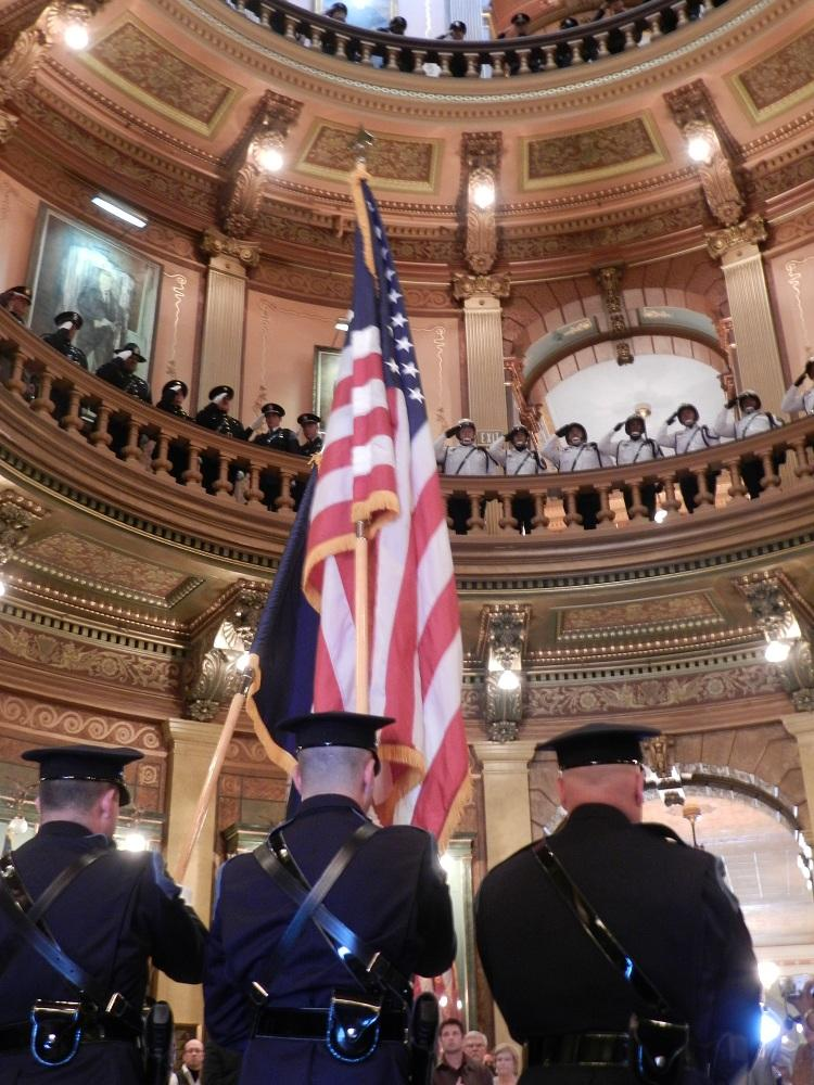 Law enforcement officers salute during a ceremony at the state capital honoring police officers who died in the line of duty.
