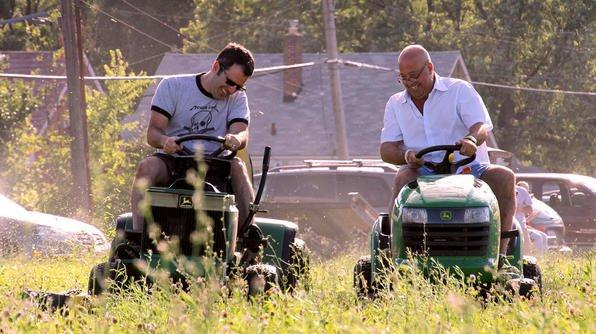 Tom Nardone and Andrew Zimmern mowing the grass at O-Shea Playground