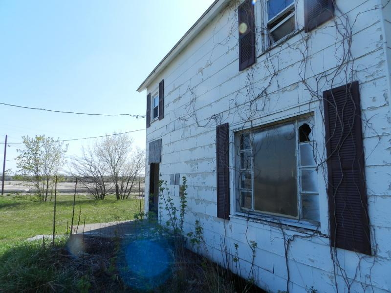 An abandoned home on Flint's northside sits in a blighted neighborhood near a paved over site of a former factory
