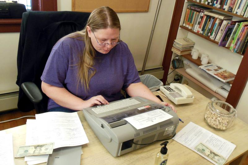 Doris Hernandez sets up a make-shift office at the church in Muskegon to type information onto the marriage licenses, which is required by state law.