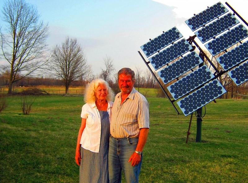 Barbara Geilser and Maynard Kauffman stand in front of the solar panel next to their home, 11 miles away from Palisades.