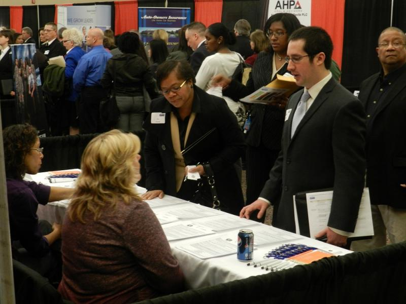 Job applicant Daniel Zanetti talks with a recruiter at the Michigan Works job fair at the Lansing Center