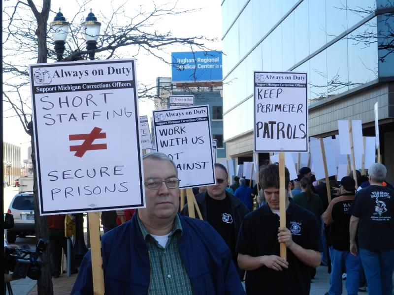 Members of the Michigan Corrections Organization picket in front of the headquarters of the Department of Corrections.