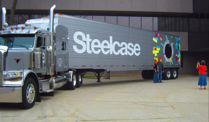 Steelcase shows off its new logo on a semi outside its headquarters.