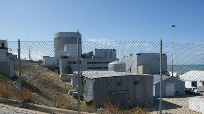 A side view of the building that hold the nuclear reactor. Security personnel (with automatic weapons) are positioned on top of some of the buildings.