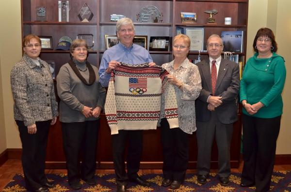 Gov. Rick Snyder is presented with an official 2014 Olympic Closing Ceremony sweater by Debra and Chuck McDermott, owners of the Stonehedge Fiber Mill in East Jordan, MI.