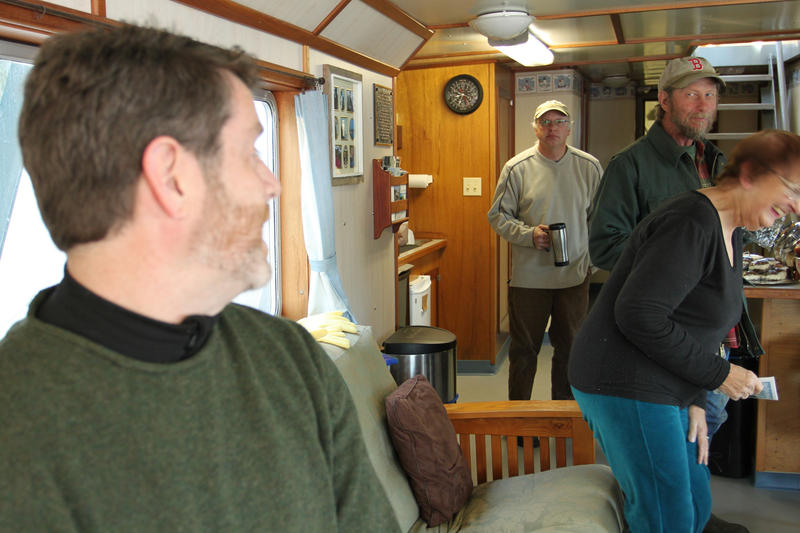Douglas Cornman, foreground, shares a laugh with islanders Bernie Barter and Leland Small, as ship engineer Storey King looks on.