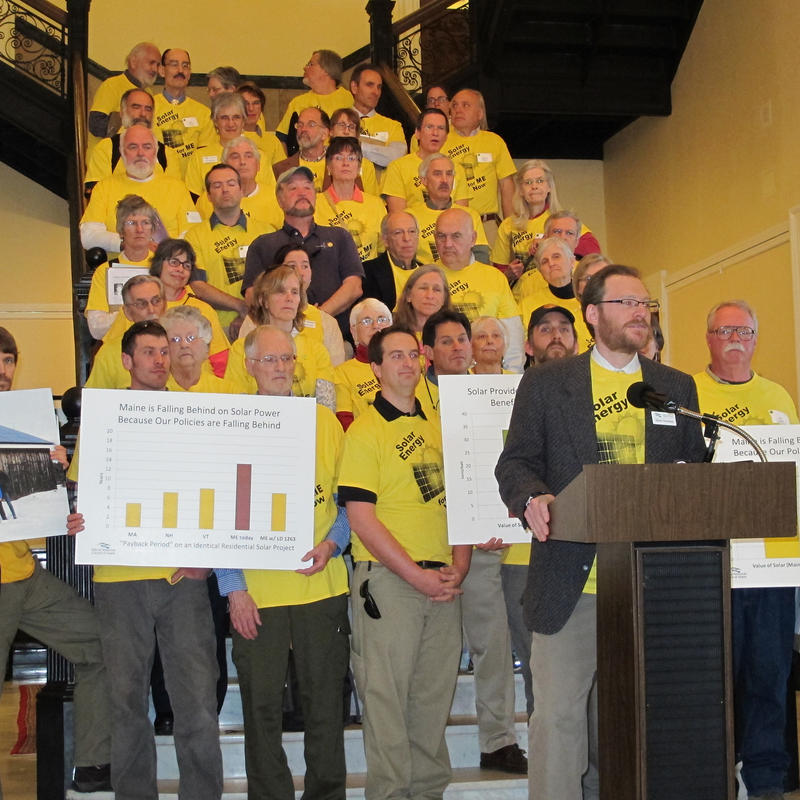 Dylan Voorhees, of the Natural Resources Council of Maine, is flanked by solar energy supporters at a State House news conference Thursday.