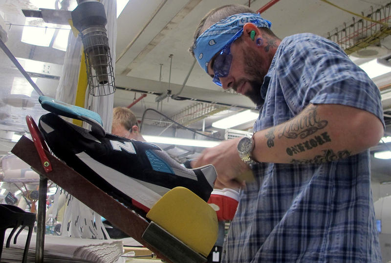 Joshua Goodridge puts the finishing touches on a pair of New Balance 998 sneakers.
