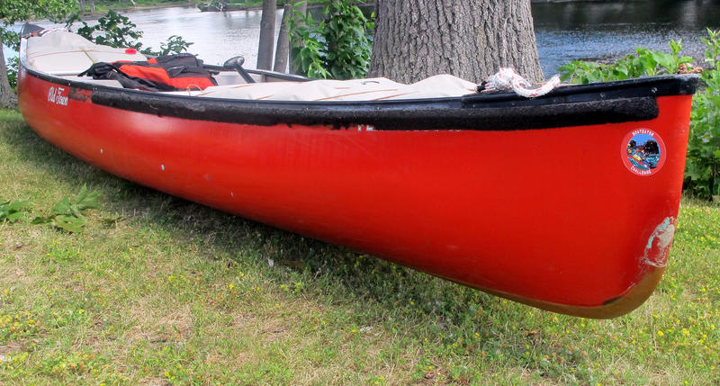 A bright red Old Town canoe sits on the river bank.