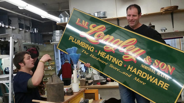 John Longley (r.) removes sign on the eve of the store's closure.