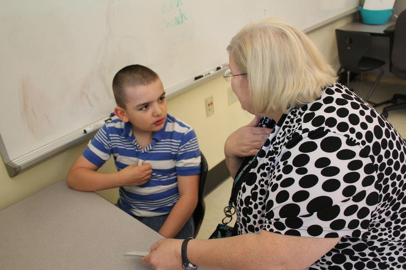 An education technician works on reading with a student, Jared, at a RISE classroom inside Lewiston's Geiger Elementary School.