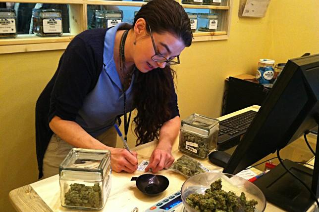 A bud tender at Northern Lights dispensary in Edgewater, Colorado, prepares a package marijuana for customer on Jan. 1, 2014. The store separates marijuana sold for medicinal and recreational use, as required by Colorado law.