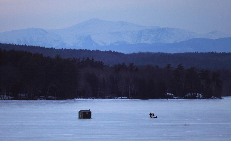 Ice fisherman head for home at dusk on Long Lake, Tuesday, Feb. 21, 2012, in Naples, Maine. Mount Washington and Presidential Range in New Hampshire can be seen 40 miles to the west.