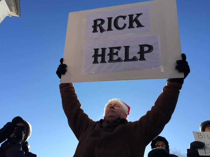 Bill Weber holds a sign appealing to Maine GOP Chairman Rick Bennett to not vote for Donald Trump during a rally of several hundred people at the State House Monday.