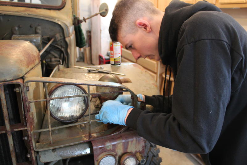Baxter Academy Sophomore Taylor Wells works on the rusted lights of a World War II-era ambulance on a recent snow day.