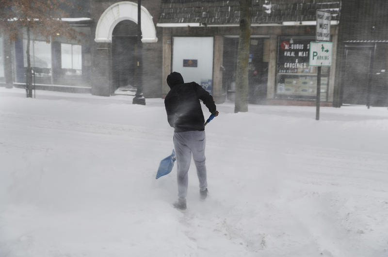 Winds whip through a downtown street in Lewiston Tuesday, as a pedestrian shovels a path for a snowed-in car.