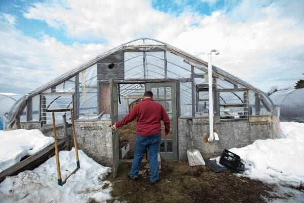 Mike Bahner enters of his hoop houses on a late winter day at Bahner Farm in Belmont.