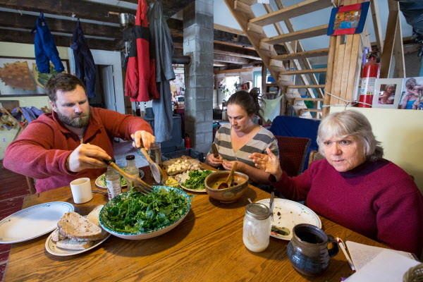 On a recent day, Slow Money Maine coordinator Bonnie Rukin (right) sat down with Mike and Christa Bahner on their farm over a lunch of fresh greens from their greenhouse.