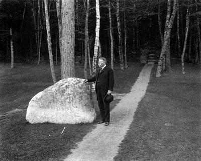 George Dorr posing at the carved rock next to the spring canopy, c.1918. A gravel path leads to the Emery Path, one of six memorial trails built at Sieur de Monts Spring in Acadia National Park c.1910s.