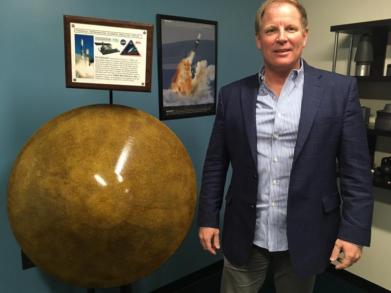 FMI President Rob Pierson stands next to a heat shield developed for the NASA Stardust mission.