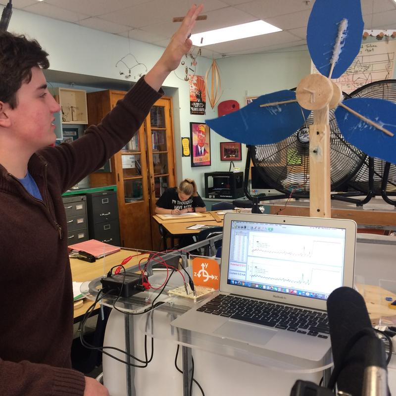 Student Joshua Willey builds a miniature wind turbine. He is using his school laptop to measure the voltage, current and resistor.