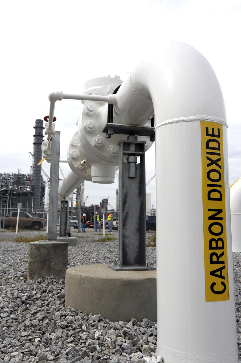 FILE - In this Oct. 21, 2013 photograph, CO2 filed pipes are secured by a barbed wire topped fence at the Kemper County energy facility near DeKalb, Miss.