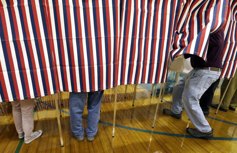 In this Nov. 8, 2016 file photo, a voter enters a booth at a polling place in Exeter, N.H.