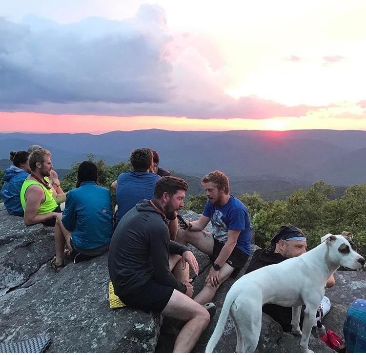 Dog Daisy joins the hikers as they watch the sun go down, next to their campsite for the night.