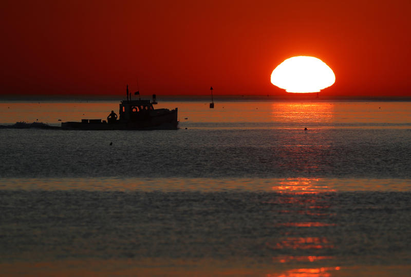 In this Wednesday, Sept. 13, 2017, photo, a lobster fishing boat heads out to sea at sunrise off Portland, Maine.
