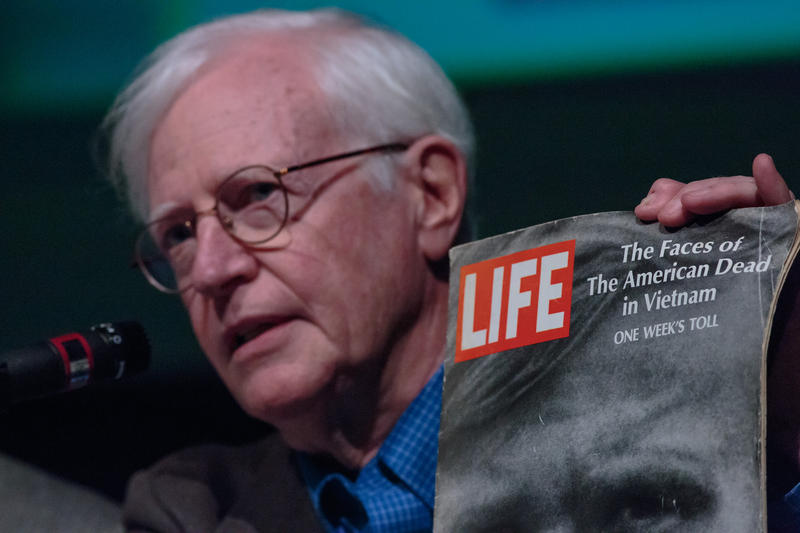 "Panelist Bill Jefferson holding up a copy of Life magazine from June 1969.  ""The Faces of the American Dead in Vietnam - one week's toll.""    During this period, 200-300 deaths were reported each week."