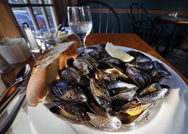 In this Wednesday, Oct. 4, 2017 photo a plate of fire-roasted mussels sits at a restaurant in Freeport, Maine.