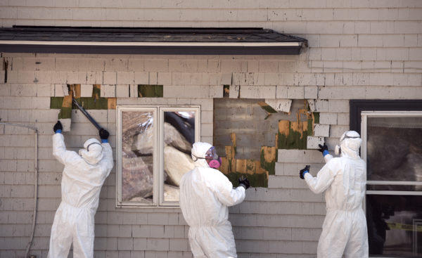 Workers remove cedar shingles, coated with lead-based paint from Jon and Briar Fishman's camp in Northport.