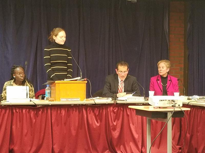 Portland School Board Chairwoman Anna Trevorrow speaks at the podium, as School Superintendent Xavier Botana, seated right, listens.