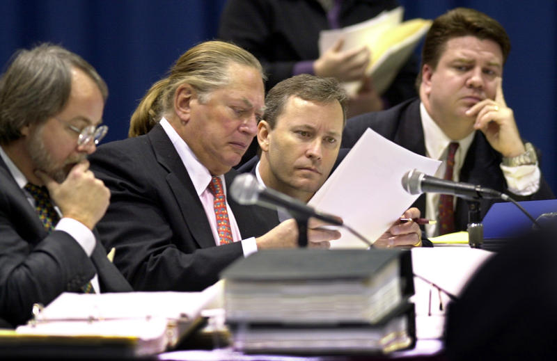Shawn Scott (third from left) examines papers during a hearing before the Maine Harness Racing Commission in Dec. 2003, in Augusta.