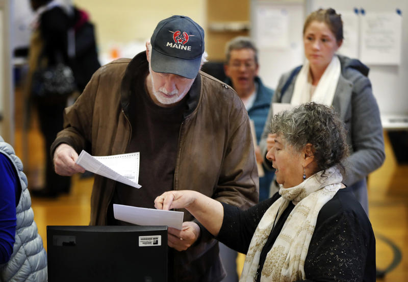 Michael Parent (left) gets instructions on submitting his ballots from warden Denise Shames while voting Tuesday, Nov. 7, 2017, in Portland.