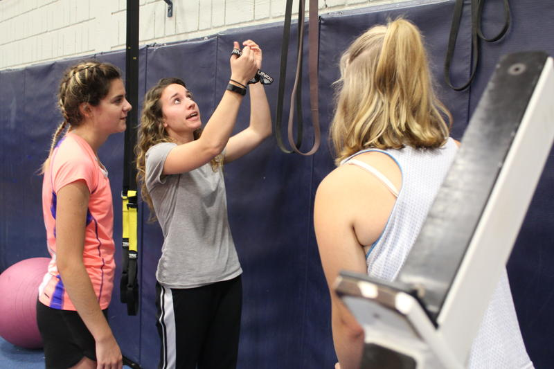 Physical education teacher Lauren Eldridge works with students on their personal fitness programs inside the gymnasium at Oak Hill High School in Wales.
