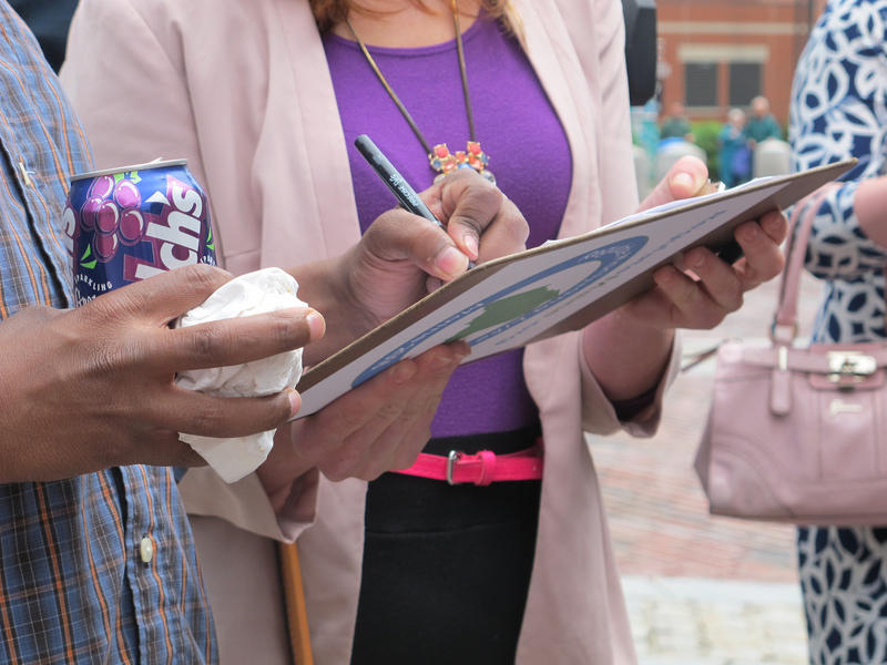 A worker gathers signatures for a petition in June 2015.