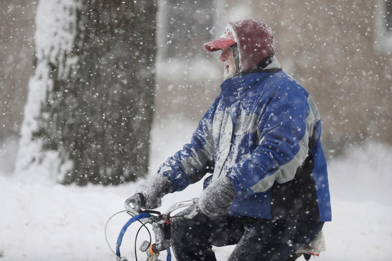A man rides on his bicycle as fresh snow falls, Friday, Dec. 29, 2017, in Erie, Pa.