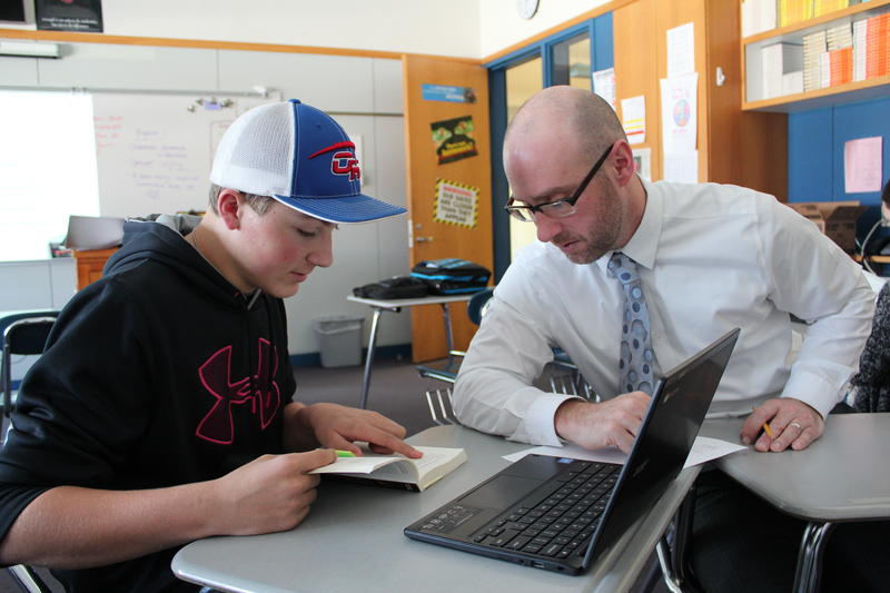 Oak Hill High School Principal Marco Aliberti works with a student in English class as part of a revamped course structure in the school.