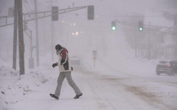 A man walks across the road in Brewer during the snowstorm on Christmas Day.