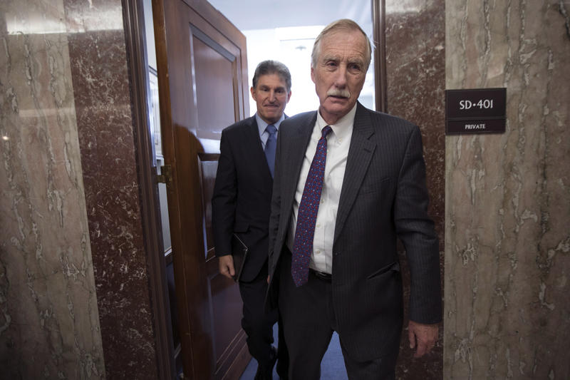 Sen. Angus King, I-Maine, right, and Sen. Joe Manchin, D-W.Va., leave the office of Sen. Susan Collins, R-Maine, who is moderating bipartisan negotiations on immigration, at the Capitol in Washington, Thursday, Jan. 25, 2018.