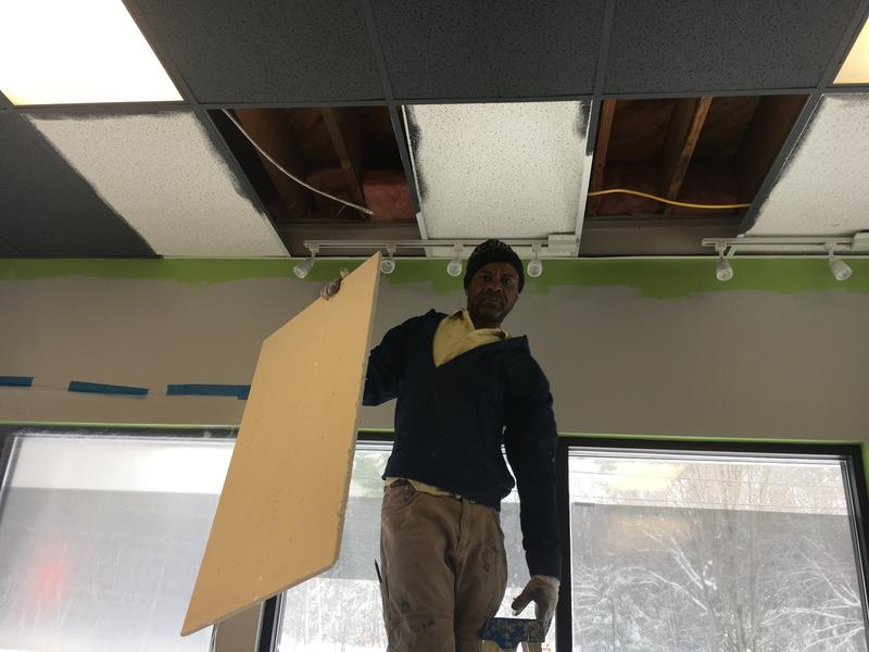 Alban Bowens works on the ceiling at a job site on Forest Avenue in Portland.