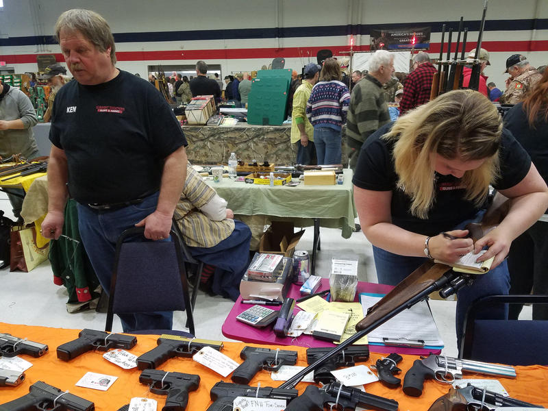 Gun dealer Kendra Lyman-Hood and her father, left, work their booth at last weekend's gun show at the Augusta Armory.