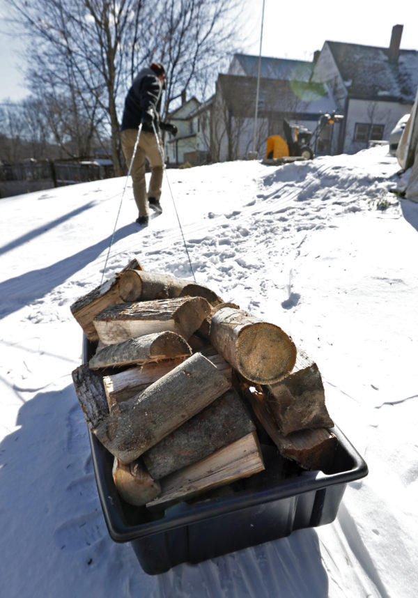 Corbin Chamberlain, 16, pulls a sled load of firewood up from the backyard, Saturday, Feb. 3, 2018, in Mechanic Falls, Maine, where the morning temperature was -1 degrees F.